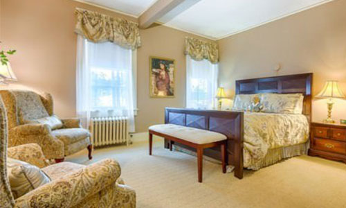 Adriana room; a room with a bed, lounge chairs, and a night stand.