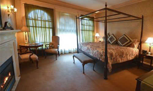 Desdemona room; A room with a bed, lounge chairs, dressers, and fire place.