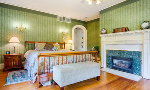 Portia room; a bed in a room with green wallpaper and a fire place.