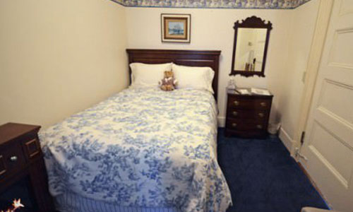 Puck bed room; single bed with blue and white sheets.