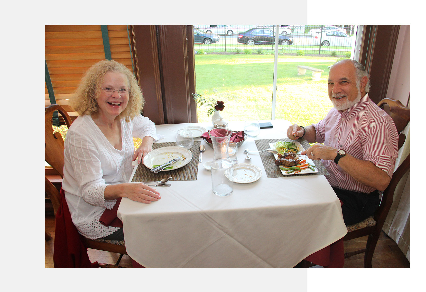 Two people sitting at dinner and smiling.