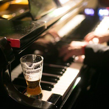 A glass of beer sitting on the edge of a piano, as someone plays the piano.