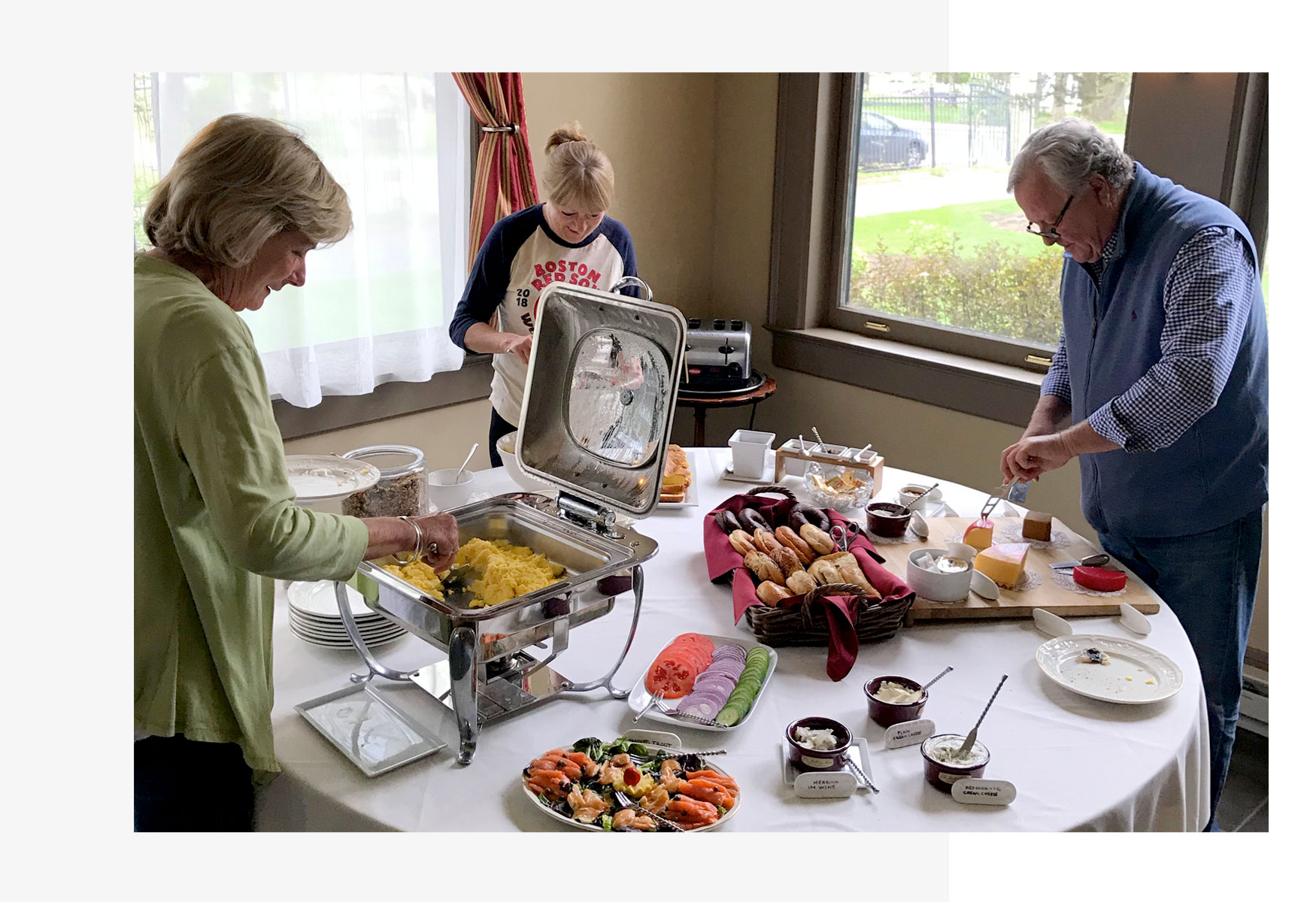 People helping themselves to the breakfast buffet.