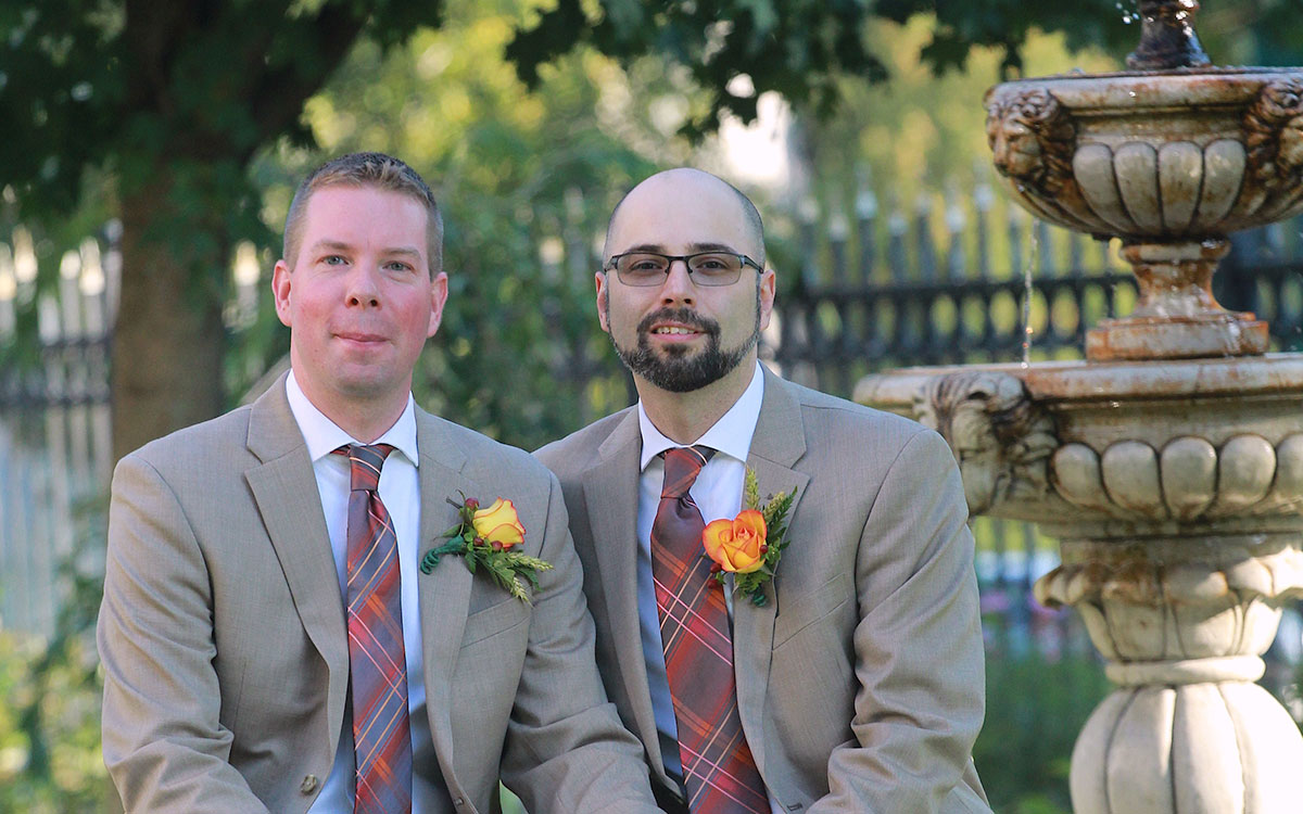 two men sitting together on wedding day.